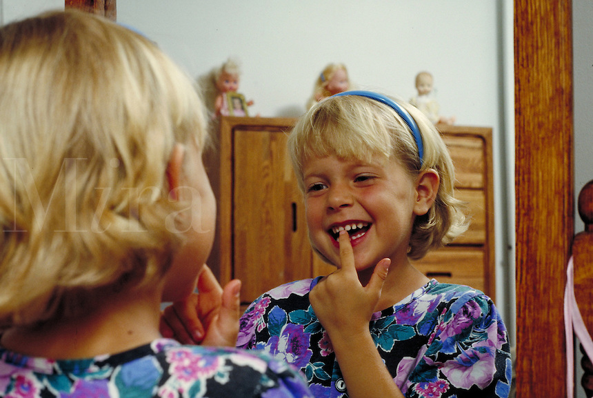 CAUCASIAN GIRL WIGGLING LOOSE TOOTH. CAUCASIAN GIRL. OAKLAND CALIFORNIA USA.