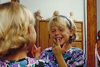 CAUCASIAN GIRL WIGGLING LOOSE TOOTH. CAUCASIAN GIRL. OAKLAND CALIFORNIA USA.