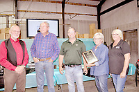 RACHEL DICKERSON/MCDONALD COUNTY PRESS D. Wayne Bearbower of the McDonald County Chamber of Commerce, left, presents Jim Cooper, Shawn Cooper, Naomi Cooper and Michelle Spears with a plaque recognizing Cooper Gear's 25 years in business at a celebration on June 13.