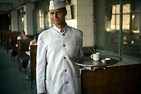 A waiter holds a tray of coffee cups in the Indian Coffee House, Baba Kharak Singh Marg, New Delhi.