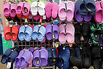 Display of colourful children's plastic Croc beach footwear at the seaside town of Cromer, north Norfolk coast, England