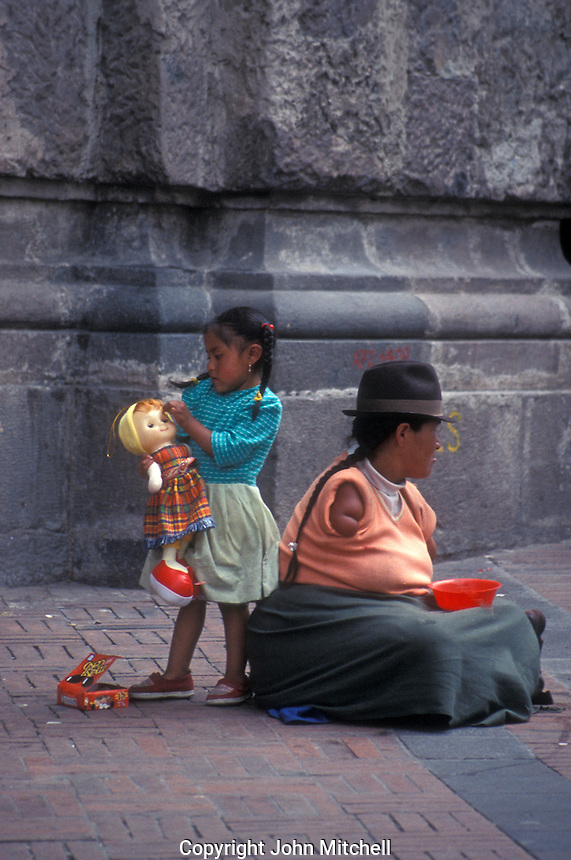 Indian woman with deformed arms begging with her daughter in the Old Town, Quito, Ecuador
