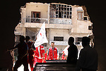 Red Crescent workers wait near to carry the bodies of dead fighters loyal to Free Syrian Army during an exchange of dead bodies between Free Syrian Army and Syrian Government forces, in Bustan al-Qasr district in the east of the northern Syrian city of Aleppo on June 11, 2015. Photo by Ameer al-Halbi