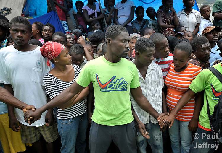 Men hold back a crowd at a food distribution in the Santa Teresa camp in Petionville, Haiti. Hundreds of families left homeless by the devastating January 12 earthquake live here. The ACT Alliance provides a variety of services in this camp.