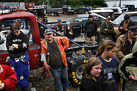 Drivers gather to hear instructions for the rules of the mud bogging competition. All ages and sexes compete by driving through mud and are timed for the fastest.