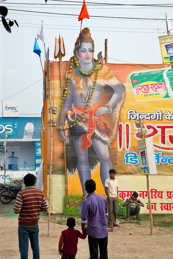 "India. Uttar Pradesh state. Allahabad. Maha Kumbh Mela. A large billboard with the Hindu God Shiva holding a trishula is used on an advertisement campaign for a detergent power. Shiva is a Hindu deity and is considered the Supreme God. A trishula is a type of Indian trident, commonly used as a Hindu religious symbol. The word means ""three spear"" in Sanskrit. In India, the term often refers to a short-handled weapon which may be mounted on a danda or staff and is wielded by the Hindu God Shiva. The Kumbh Mela, believed to be the largest religious gathering is held every 12 years on the banks of the 'Sangam'- the confluence of the holy rivers Ganga, Yamuna and the mythical Saraswati. The Maha (great) Kumbh Mela, which comes after 12 Purna Kumbh Mela, or 144 years, is always held at Allahabad. Uttar Pradesh (abbreviated U.P.) is a state located in northern India. 6.02.13 © 2013 Didier Ruef"