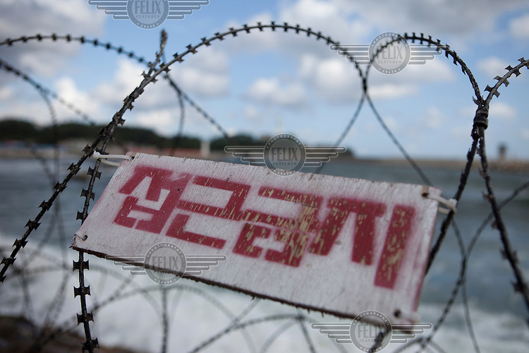 Barbed wire fences on the coast close to the DMZ (Demilitarized Zone) marking the border with North Korea.