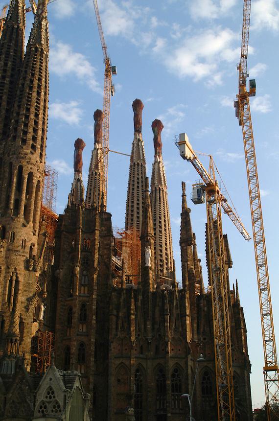 Spires of Antoni Gaudi's La Sagrada Familia cathedral with construction cranes in Barcelona, Spain.