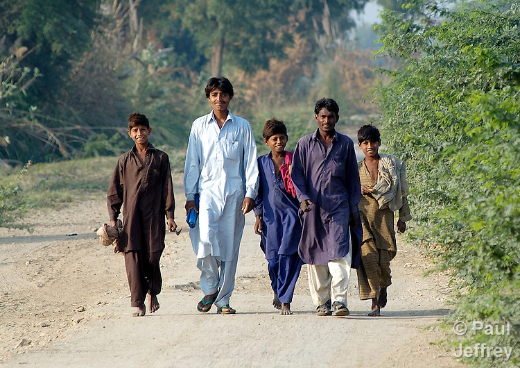 Villagers walk along a rural road in the Lower Sindh River Valley in Pakistan..