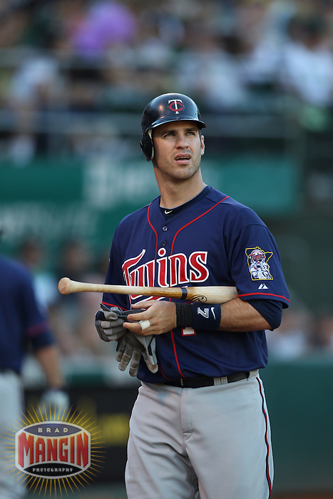 OAKLAND, CA - JUNE 5:  Joe Mauer #7 of the Minnesota Twins walks to the dugout during the game against the Oakland Athletics at the Oakland-Alameda County Coliseum on June 5, 2010 in Oakland, California. Photo by Brad Mangin