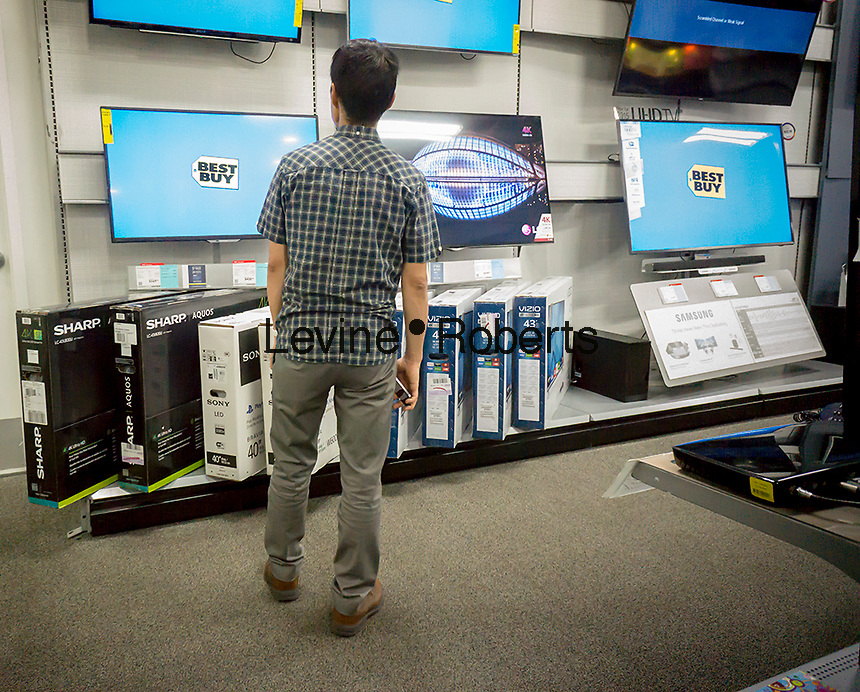 A customer browses the popular Vizio brand and other flat-screen televisions in a Best Buy in New York on Monday, July 27, 2015. Vizio filed its Form S-1 with the SEC in preparation for an initial public offering. The company manufactures budget-friendly flat screen televisions available in over 8000 retailers in the U.S. It also tracks your watching habits on its internet enabled televisions collecting viewing habits which it can monetize to advertisers.  (© Richard B. Levine)