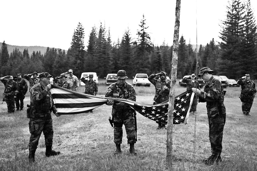 Members from multiple battalions of the Light Foot Militia salute the American flag while Willard Protsman, Robert Steiner, and Randall Klein remove it from the makeshift flagpole and fold it up at the conclusion a weekend long training event at a Civilian Conservation Corps. camp near Priest River, Idaho.