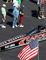 Sep 14, 2013; Charlotte, NC, USA; Fans look on at the car of NHRA top fuel dragster driver Steve Torrence and an American flag during qualifying for the Carolina Nationals at zMax Dragway. Mandatory Credit: Mark J. Rebilas-