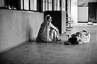 A woman sits on the floor next to a Tuberculosis patient at the Rajan Babu TB hospital in New Delhi, India.
