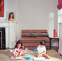 Philip Gorrivan's children sit drawing on the floor of the family room in front of a banquette upholstered in striped velvet