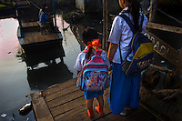 14 year old Eliyani and her younger sister, both students at Kartini Emergency School, wait for a raft to take them across the river in the slum area where they live. Since the early 1990s, twin sisters Sri Rosyati (known as Rossy) and Sri Irianingsih (known as Rian) have used their family inheritance to set up and run 64 schools in different parts of Indonesia, providing primary education combined with practical skills to some of the country's most deprived children.