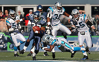 Seattle Seahawks running back Shaun Alexander (37)runs past Carolina Panthers Mike Minter (30), Colin Branch (28) and Dan Morgan for a first down in the game on Oct. 31, 2004 at Qwest Field in Seattle. The Seattle Seahawks defeated the Carolina Panthers.