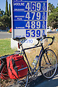 A commuting bicycle beside a gas price list showing high prices on June 11, 2008. Cupertino, California, USA