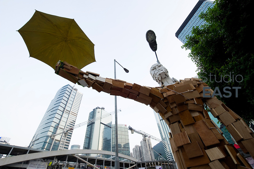 HONG KONG, HONG KONG SAR, CHINA - OCTOBER 13: The Umbrella man statue has become a symbol in the 'Occupy Central' camp on Connaught road, Admirality, Hong Kong, China, on October 13, 2014. Hundreds of men attempted to break through barricades erected by Hong Kong pro-democracy protesters near the city's business district, as a third week of rallies tried the patience of truck and cab drivers. 'Occupy Central' protesters rebuilt barricades to make sure Queensway stayed theirs. The 'Umbrella revolution' or 'Occupy Central' is a civil disobedience movement that began in response to China's decision to allow only Beijing-vetted candidates to stand in the city's 2017 election for the top civil position of chief executive. Thousands of pro-democracy supporters are calling for open elections and the resignation of Hong Kong's Chief Executive Leung Chun-ying. (Photo by Lucas Schifres/Getty Images)