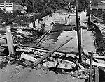 The concrete section of Huntingdon Avenue bridge looked as if it might have been stepped on by Paul Bunyan. The railroad tracks underneath are twisted and torn, and the river is peaceful now. The steel section over the Naugatuck River remained intact, and was being used yesterday by CL&P crews. 25 August 1955.