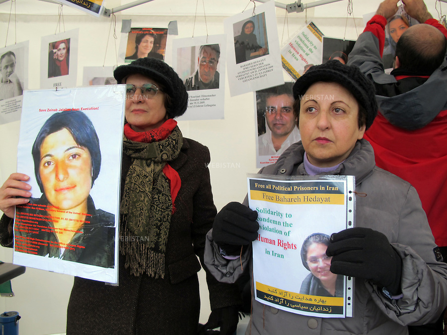 """Switzerland. Geneva.UN headquarters. December 2010: A sit-in outside the UN headquarters in Geneva by a group of women's rights activists to draw attention to Nasrin Sotoudeh,  the jailed lawyer in Iran. Khadijeh Moghaddam (on the left)  and Shirin Ebadi (on the right) and holding photos of  """"Zeinab Jalalian"""" (Kurdish political prisoner) and """"Bahareh Hedayat"""" (imprisoned student activists currently on hunger strike) respectively."""