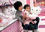 A little girl and her mother hold Hello Kitty soft toys during  the opening of Hello Kitty's Kawaii (Cute) Paradise, a Hello Kitty theme store, in Tokyo, Japan on Thursday 21 October  2010. .Photographer: Robert Gilhooly