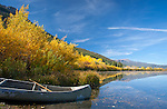 Montana, Southwest, Beaverhead county, Centennial valley. A canoe on the shores of Upper Red Rock Lake lined with golden autumn foliage.