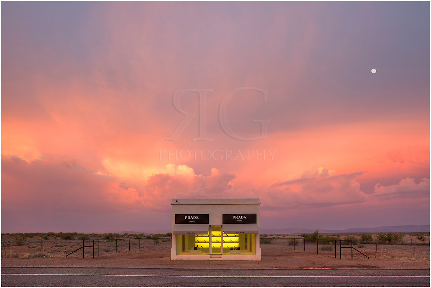 Between Van Horn and Valentine, Texas, a long US Highway 90 in the Chihuahuan desert, sits a permanent display of adobe brick, plaster, paint, glass, and several prada shoes and bags provided by the one and only Miuccia Prada. This West Texas image was captured a little before sunrise. I arrive early, and while driving south from Van Horn, Texas, I feared the clouds would blanket everything in a dull gray. Amazingly, as the sun rose in the east, the sky in front of me lit up with large thunderheads and everything turned pastels of orange and purple.<br />