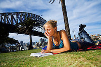 A young woman reads a book on the lawn at Dawes Point Reserve on Sydney harbour.