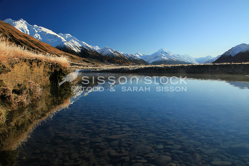 Mount cook and the southern alps reflected in the Tasman river early morning.
