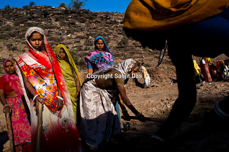 Women work at a site as part of NREGA at Gobra Ki Nari Mein site near the Khori Bijasan Devi Temple in Karauli district of Rajasthan, India. The National Rural Employment Guarantee Act (NREGA) that has created a source of additional income for families living below the poverty line by providing a minimum 100 days of employment assured under the Act. Photo by Sanjit Das