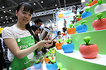 July 15, 2010 - Tokyo, Japan - A booth assistant introduces the 'Flip Flap Solar Powered Apple Green ' during the International Tokyo Toy Show 2010 at Tokyo Big Sight, Japan, on July 15, 2010.The toy fair, held from July 15 to July 18, attracts buyers and visitors by introducing the latest products presented by various toymakers from Japan and abroad.