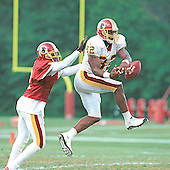 Washington Redskins cornerback Deion Sanders (21) reaches for wide receiver Michael Westbrook (82) as he attempts to pull in a Brad Johnson pass as the team begins the third week of training camp at Redskins Park in Ashburn, Virginia on August 1, 2000.<br /> Credit: Arnie Sachs / CNP