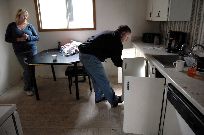 A City of Regina bylaw standards officer makes photographs Deanne Desjarlais's kitchen before informing her the rental home is unfit for human habitation and that she must move out immediately. MARK TAYLOR GALLERY