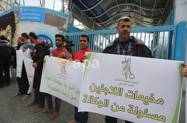 Palestinians hold banners during a protest to demand UNRWA provide electricity to refugee camps, in Gaza city, on April 23, 2017. Photo by Mohammed Asad