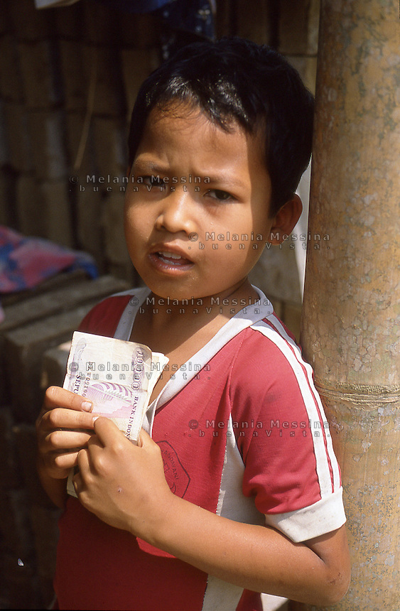 Indonesia, Java island:child holding the wages of workers <br /> Indonesia; Giava: bambino tiene in mano le paghe degli operai