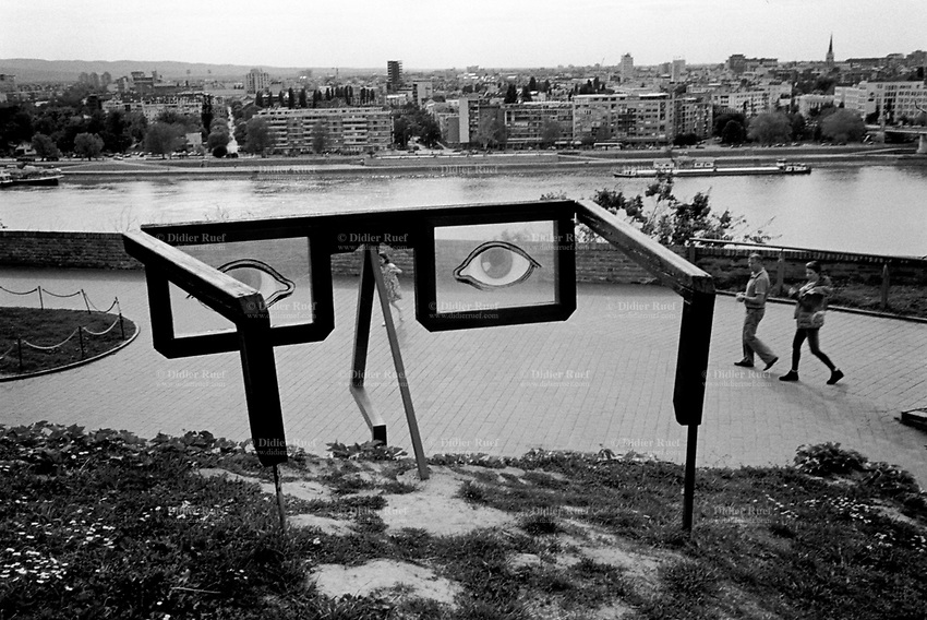 Serbia. Province of Vojvodina. Novi Sad. View from the Petrovaradin Fortress on Novi Sad and the Danube river.  A family with daughter visits the Fortress. A local artist has created a work of art, a wooden scuplture with the shape glasses and two painted eyes. Novi Sad is the second largest city of Serbia, the capital of the autonomous province of Vojvodina and the administrative center of the South Bačka District. It is on the banks of the Danube river. Petrovaradin Fortress is a fortress in the town of Petrovaradin, itself part of the City of Novi Sad, It is located on the right bank of the Danube river. The cornerstone of the present-day southern part of the fortress was laid on 18 October 1692 by Charles Eugène de Croÿ. Petrovaradin Fortress has many underground tunnels as well as 16 km of uncollapsed underground countermine system. 26.4.2017 © 2017 Didier Ruef
