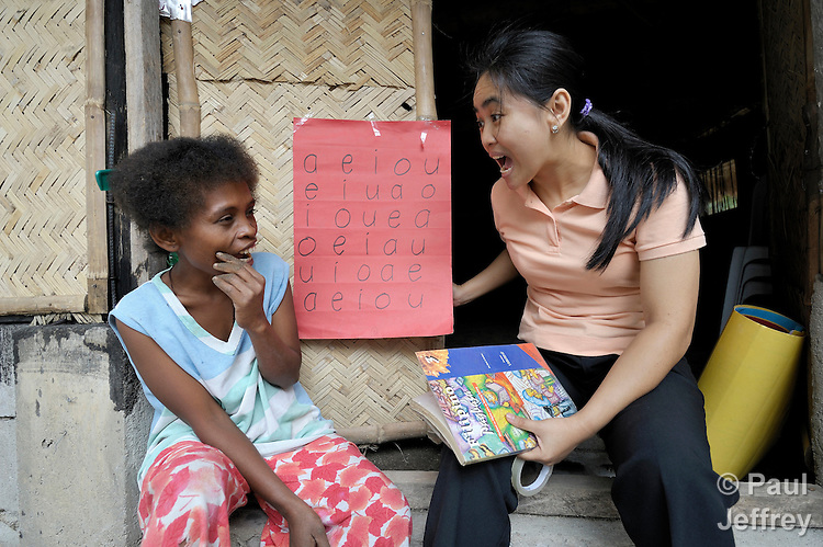 United Methodist Pastor Leslie Dela Cruz, right, teaches basic literacy, including making vowel sounds, to Janet Tamtan, an Aetna indigenous woman in the Philippine village of Camachile, where the United Methodist Church has a pastoral presence among Aetnas who were displaced by the eruption of Mt Pinatubo.