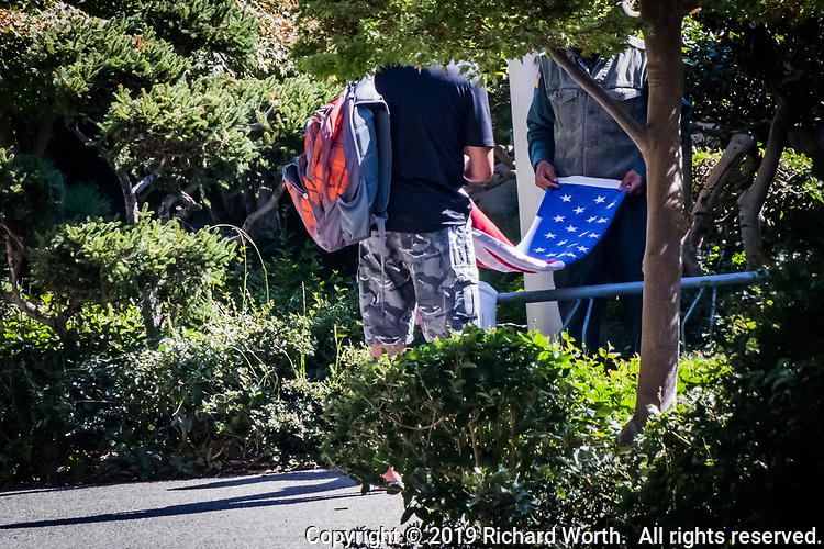A park employee has enlisted the help of a volunteer, a visitor, and has tasked him with properly beginning the process of folding the US Flag that has just been lowered from the flag pole.