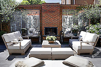 Comfortable seating is grouped around an outdoor fireplace on the teak decking of the terrace