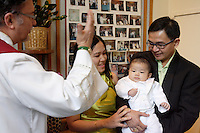 Montreal (qc) CANADA -November 2009 file Photo-<br /> A Filipino baby boy get baptized by a Catholic priest<br /> (model releases signed by parents only , for editorial use)