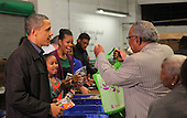 United States President Barack Obama, Sasha Obama, and First Lady Michelle Obama fill bags with produce at the Capital Area Food Bank in North East Washington DC on Wednesday, November 23, 2011. .Credit: Dennis Brack / Pool via CNP