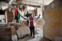 After a six month revolution, rebel forces finally managed to break into Tripoli and have taken control of Bab al-Aziziyah, Col Gaddafi's compound and residence. Few remain that are loyal to Gaddafi in the city; it is seeming that the 42 year regime has come to an end. Gaddafi is currently on the run. Two men celebrate as they stand in one of the rooms inside the compound.