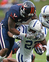 Virginia safety Brandon Woods (17) grabs the facemask of Duke running back Jay Hollingsworth (27) during an ACC football game Saturday in Charlottesville, VA. Duke won 28-17. Photo/Andrew Shurtleff