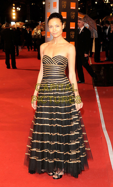 THANDIE NEWTON .The Orange British Academy Film Awards 2009, Royal Opera House, Covent Garden, London, England, February 8th 2009..BAFTAS arrivals full length black gold striped dress strapless stripes tulle .CAP/FIN.©Steve Finn/Capital Pictures
