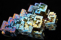 Artificially grown bismuth crystals with a characteristic  iridescent oxide tarnish displaying many colors. Bismuth is a metal and chemical element with the atomic number 83 and symbol of Bi.  In nature, it is rarely found in a native or crystal form.