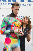 London, UK. 12 April 2015. A makeup artist applies bodypaint to a model. United Makeup Artists Expo (UMAe),  the UK's leading aspiring and professional hair and makeup artist trade show, at the Business Design Centre in Islington, London, UK. It runs until Sunday, 12 April. At this trade show leading professionals provide demonstrations and the latest techniques and products are showcased.
