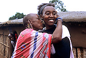 Lolgorian, Kenya. Elderly Maasai woman greeting her daughter, returned from the city for the Eunoto coming of age ceremony.