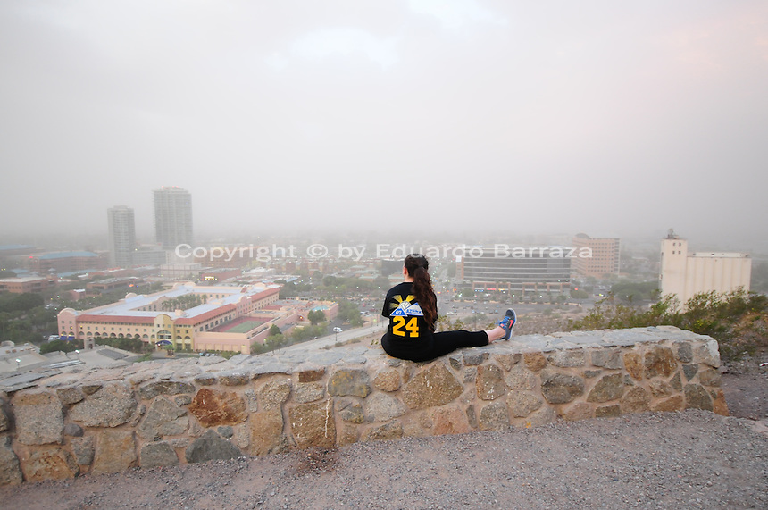 "Phoenix, Arizona (September 6, 2014) -- A young woman takes a break from her hiking in the ""A"" Mountain in city of Tempe to watch the dust storm blowing through the Phoenix metropolitan area. A massive dust storm sweeps into the Phoenix metropolitan area blanketing the Valley. The phenomenon created a massive wall of dust, also called ""baboob"". The dust storm was followed by thunderstorms producing very heavy rain.  Photo by Eduardo Barraza © 2014"