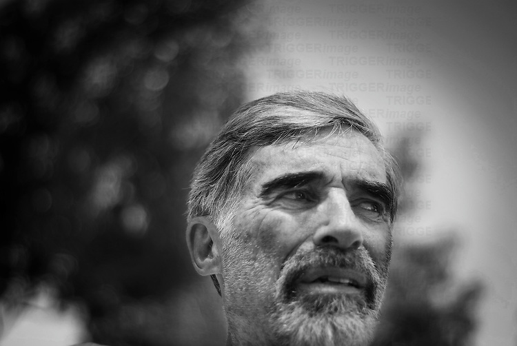 a pensive senior man looking off camera with a skeptical worried anxious look on his face, black and white, horizontal composition and selective focus